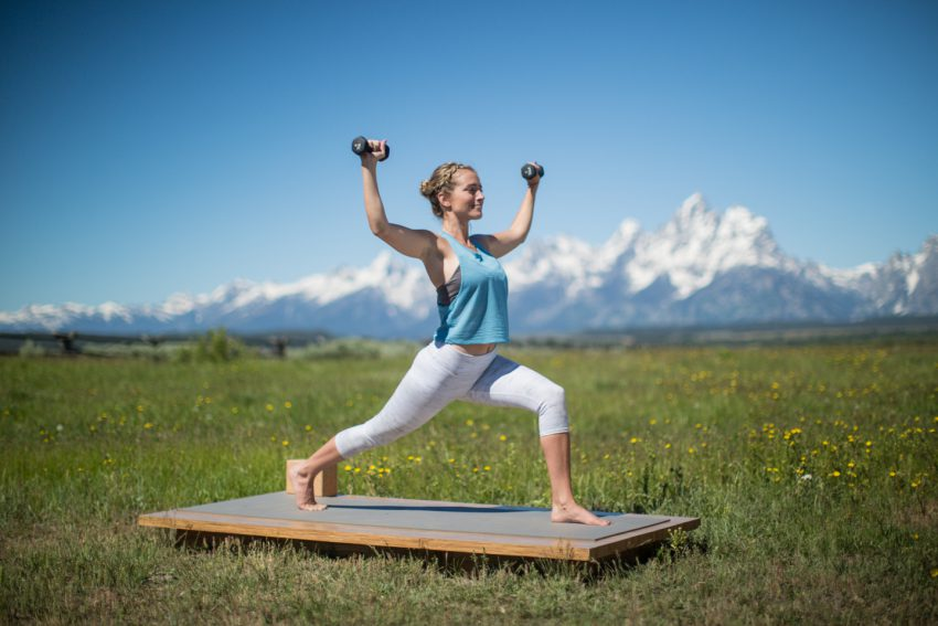 woman practices lunge pose with weights
