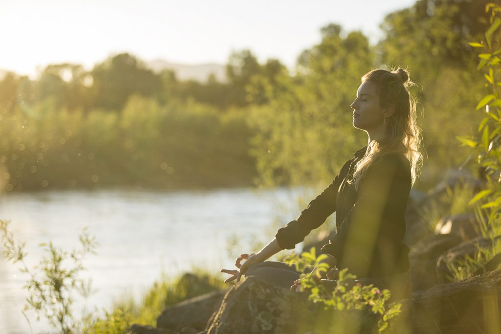 Woman meditates on the back of a river surrounded by greenery