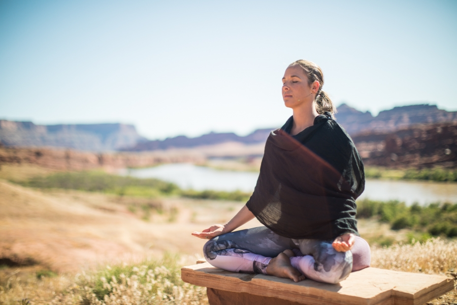 woman meditates in a desert setting