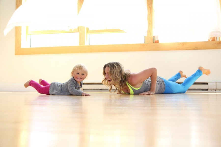 mom and child practice yoga together in a studio