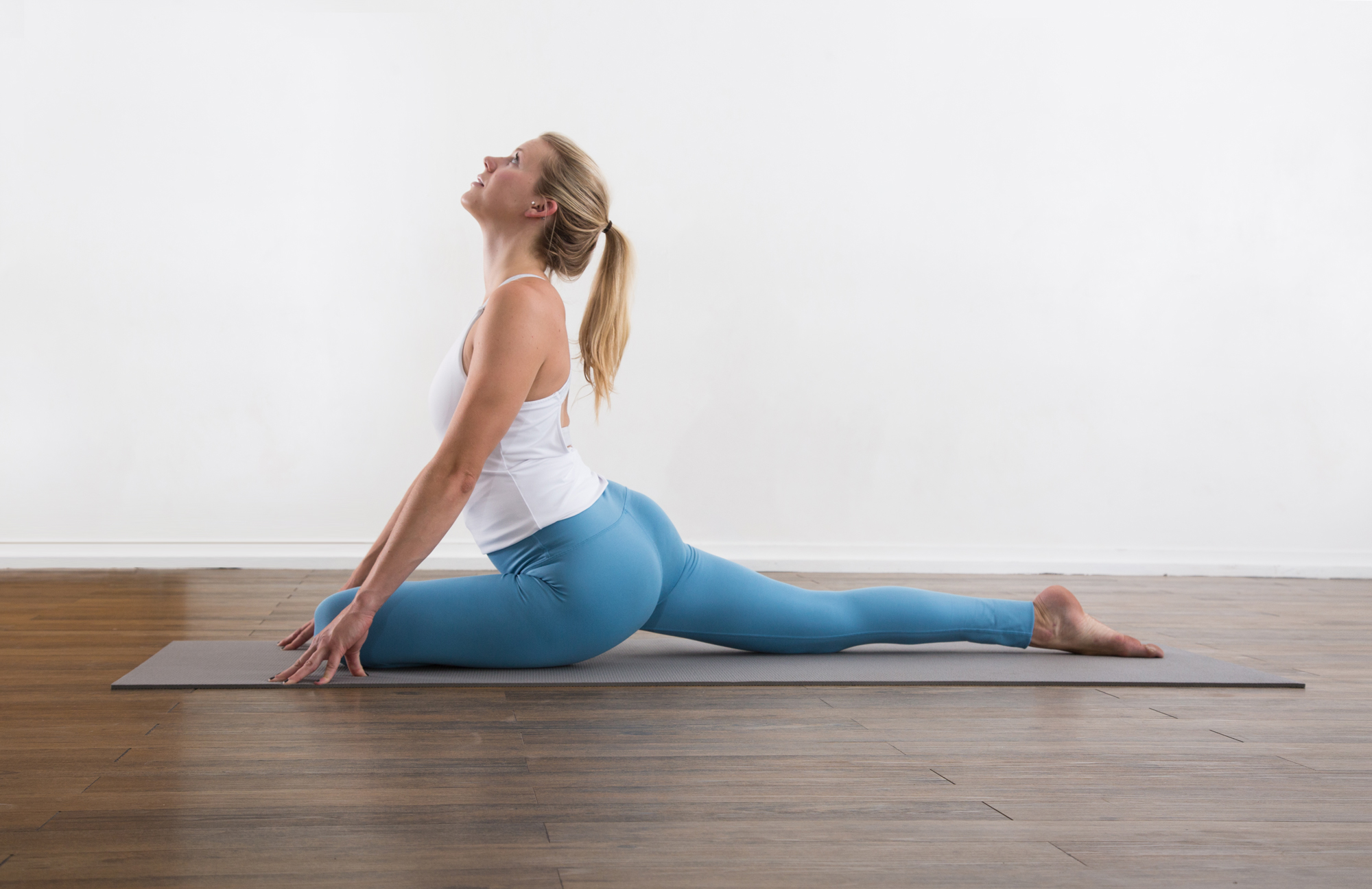 blond yogatoday Woman in a white shirt and blue pants doing yoga in a studio half pigeon pose is a deep hip stretching yoga posture