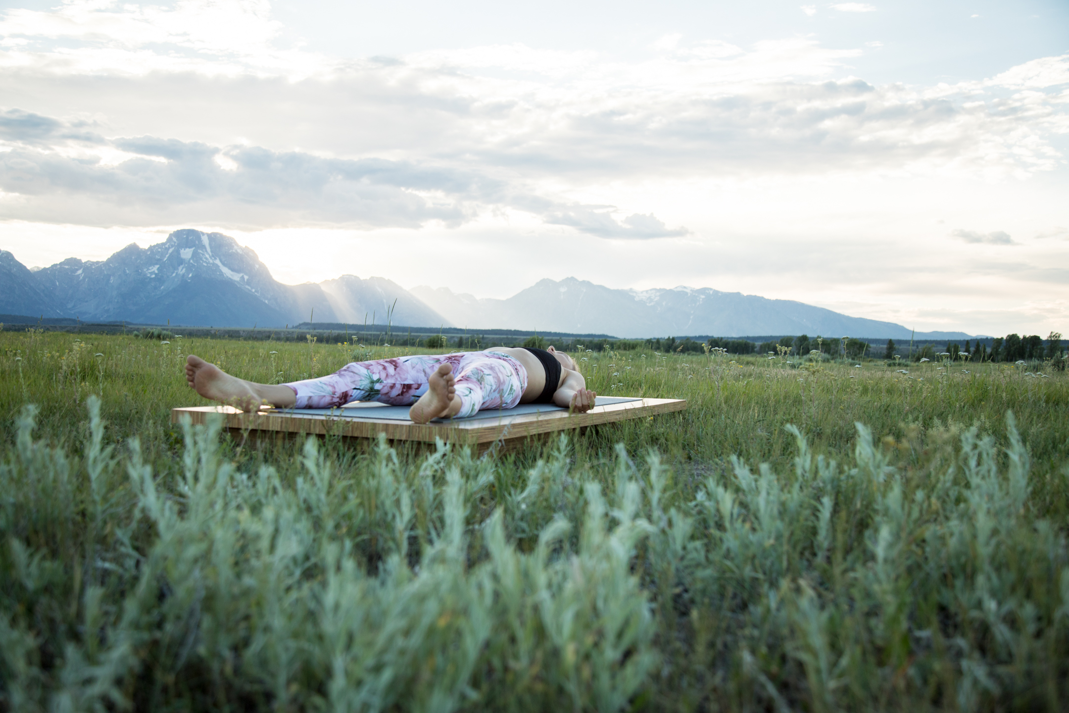 woman lies in savasana yoga pose outdoors