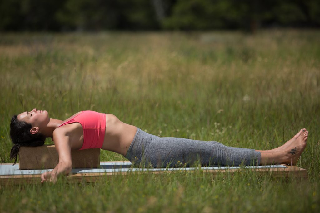Woman lowers her stress and cortisol levels by relaxing on yoga props