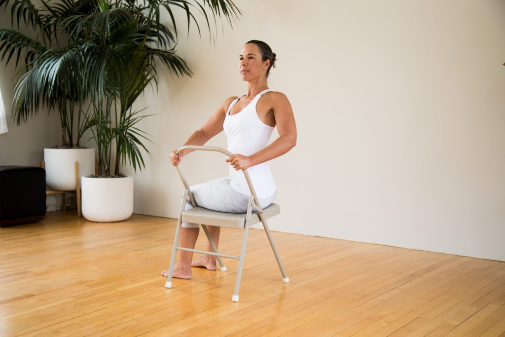 Woman does a spinal twist on a yoga chair