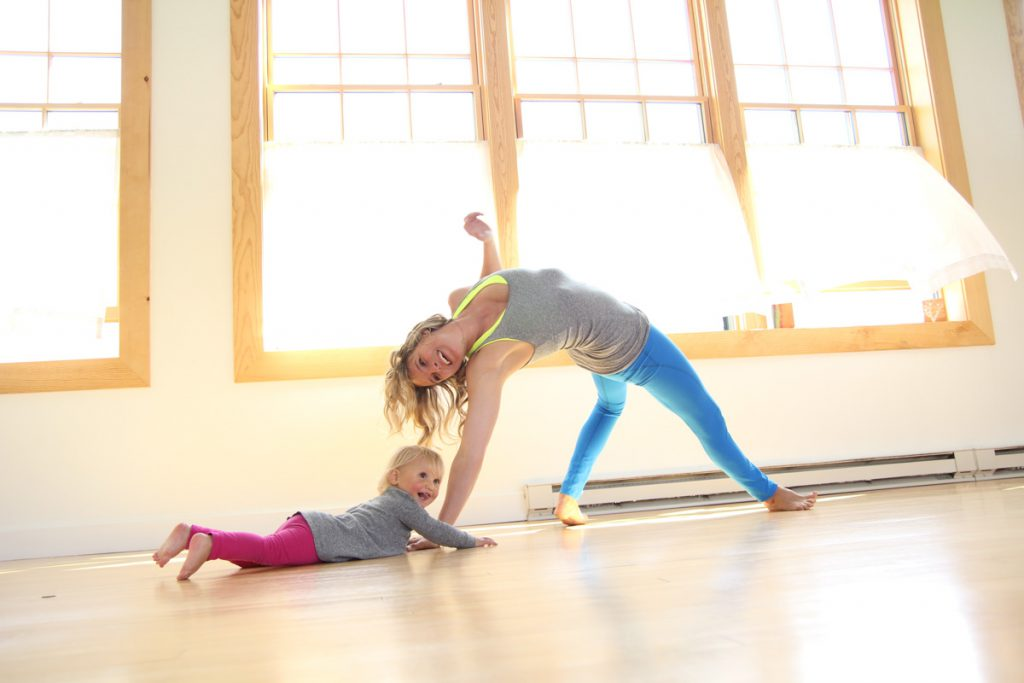 mom and young daughter practice yoga together in a sunlit room