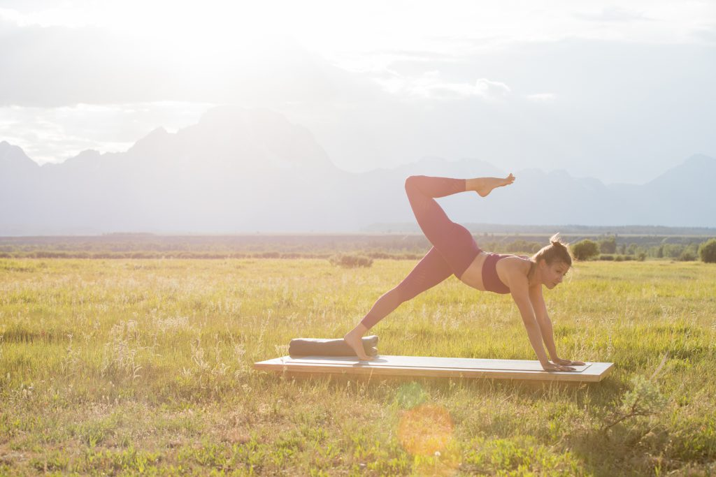 a woman practices yoga outdoors in Grand Teton National Park