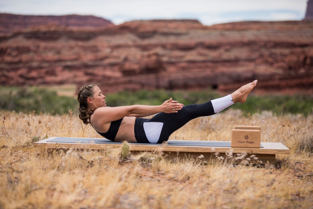 yoga teacher practices boat pose for core stability