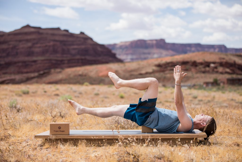 man practices a bridge pose modification to strengthen the core