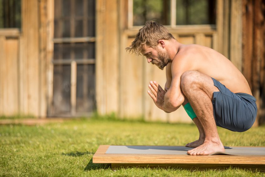 man practices yoga squat for gut health