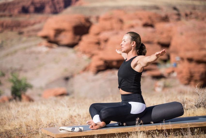 woman extends her arms in a seated yoga pose -yogatoday