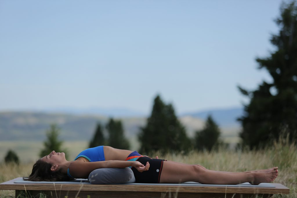 woman practices savasana at the end of yoga class - yogatoday