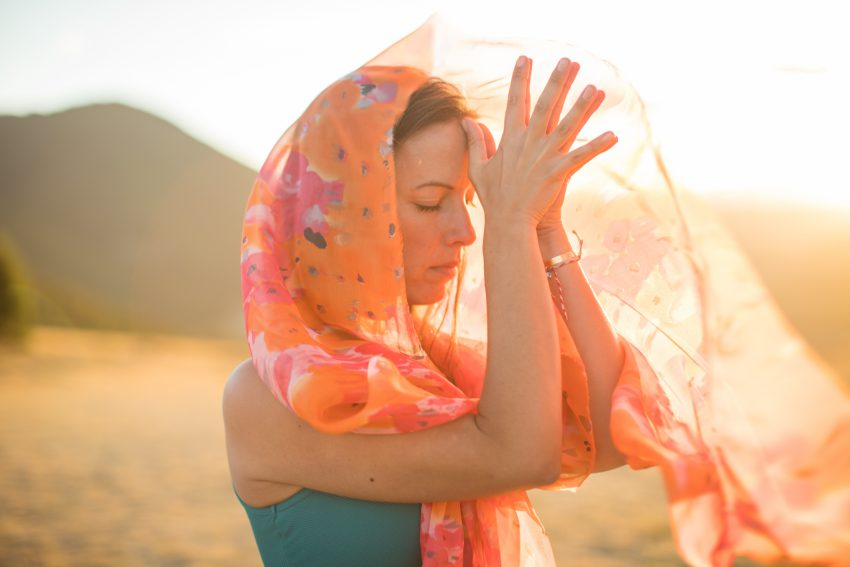 woman with orange scarf presses her thumbs to the center of her forehead - yogatoday