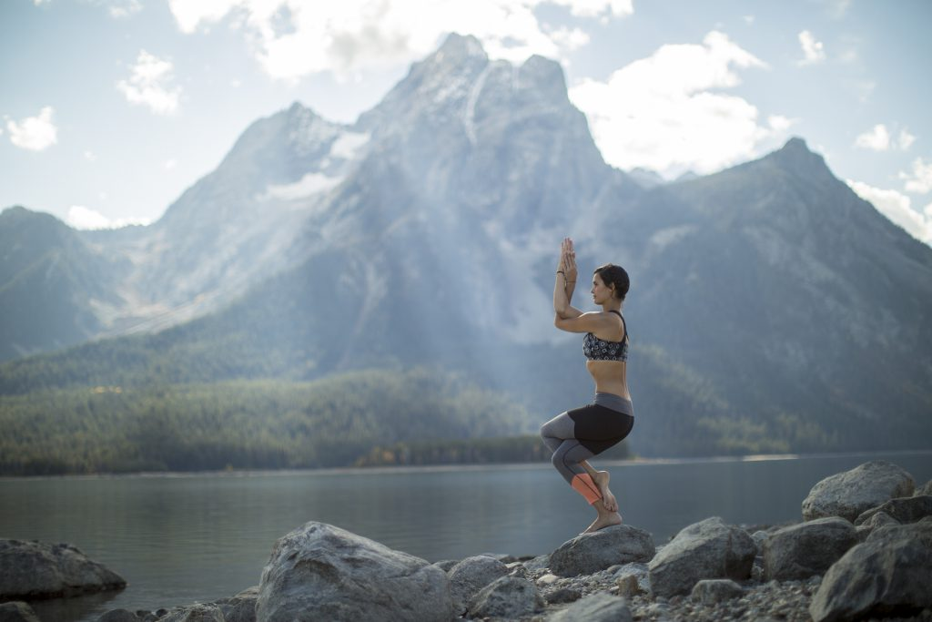 woman practices eagle pose in Grand Teton National Park -yogatoday