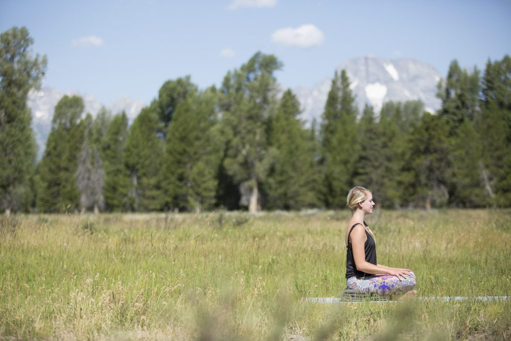 woman meditates while seated on an outdoor yoga platform in Grand Teton National Park -YogaToday
