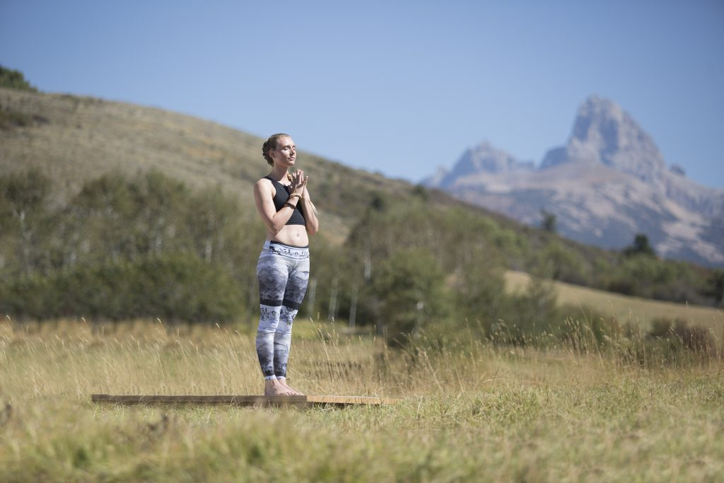 woman stands and meditates in a mountain setting - YogaToday