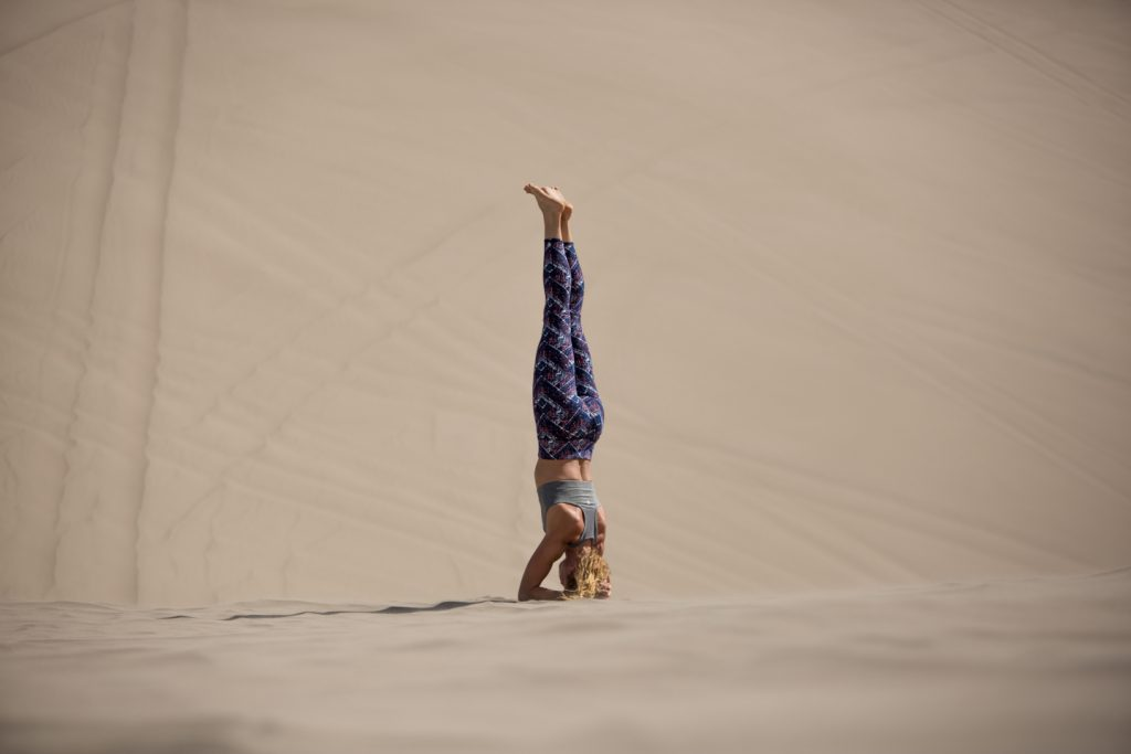 woman practices head stand in desert dunes - YogaToday