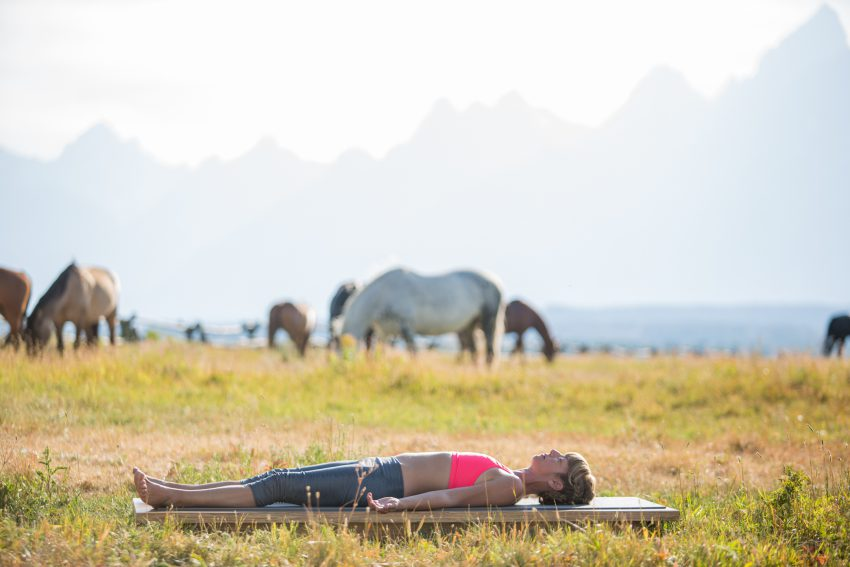 woman practices final resting pose in Grand Teton National Park - YogaToday