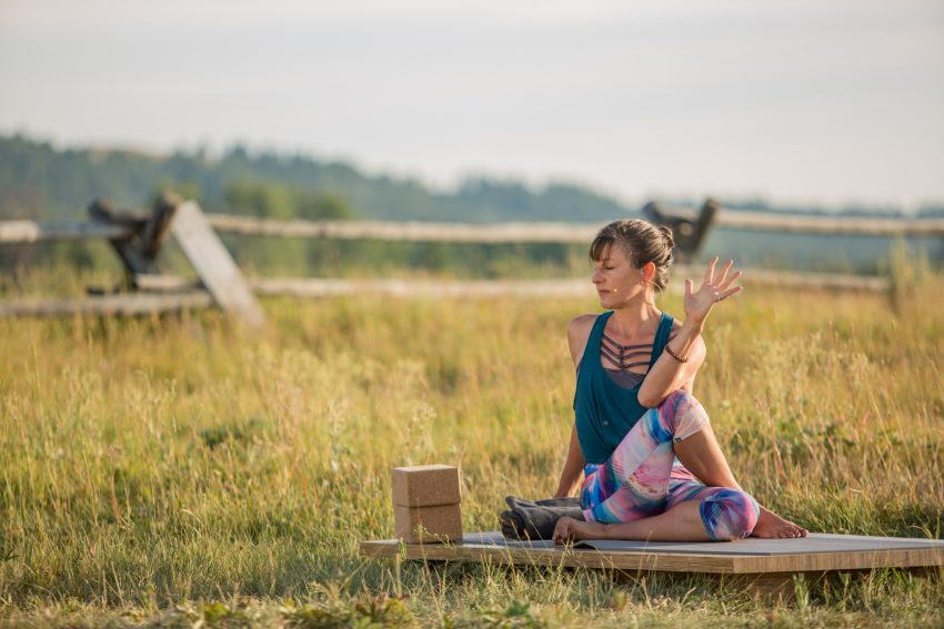 woman practices yoga outdoors to prepare for meditation