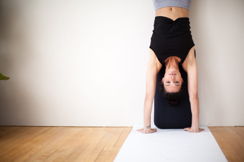 woman practices handstand inversion against a walll