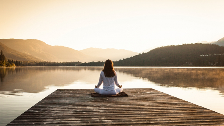 woman practices pranayama and meditation on a dock at sunrise