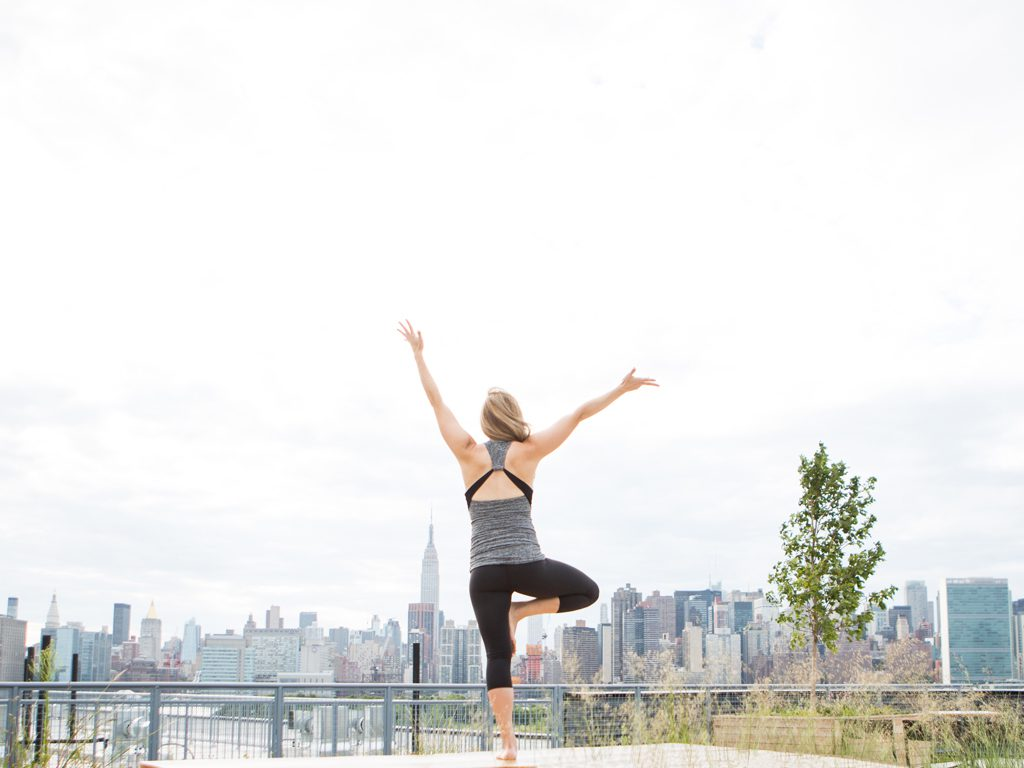 pregnant woman practices tree pose on a deck in New York City
