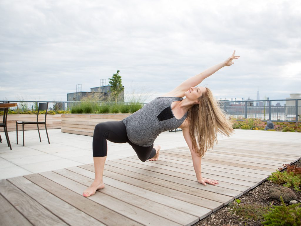 pregnant woman practices a prenatal yoga pose low lunge variation