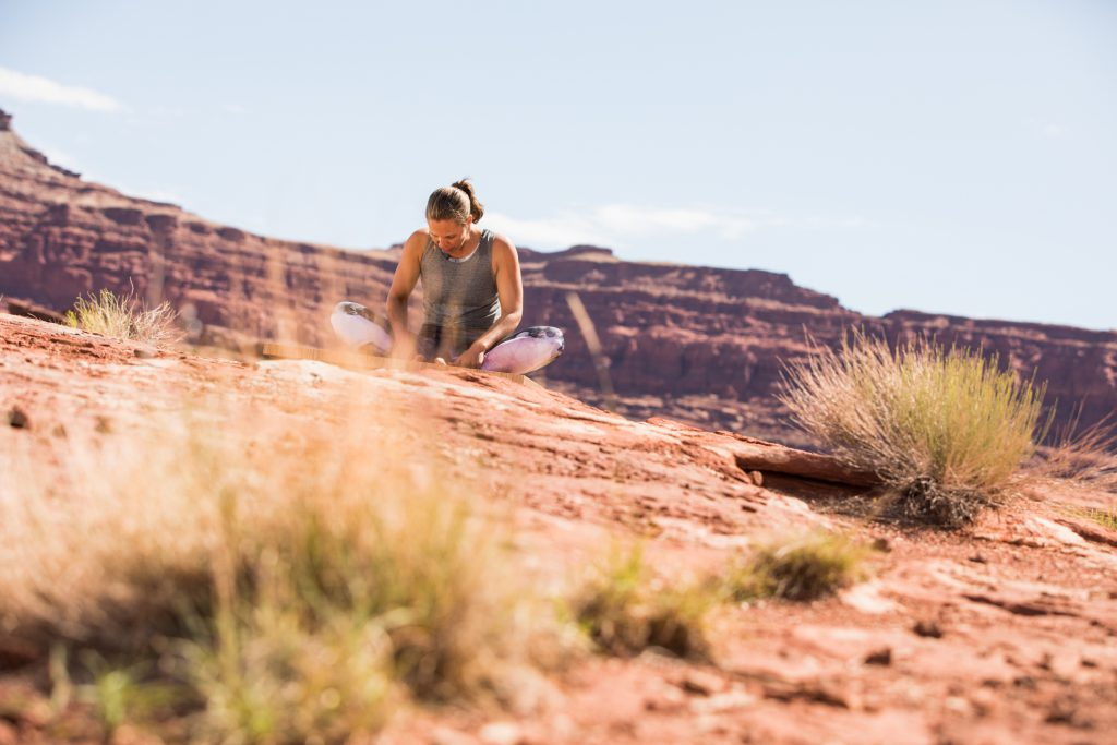 woman prepares fro meditation with a yoga pose while seated in the Utah dessert