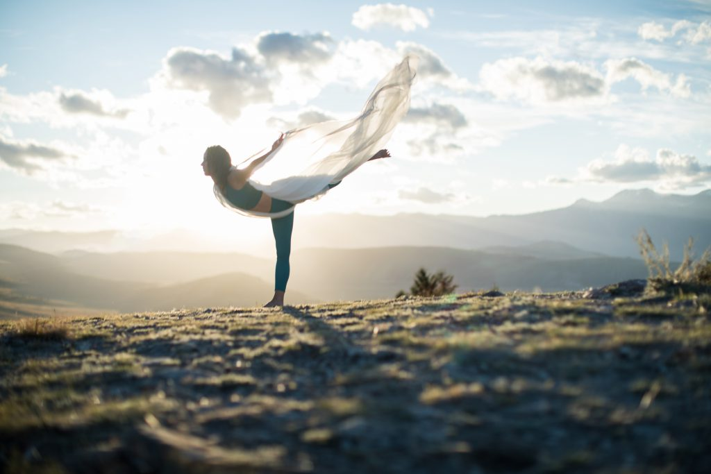 woman practices intentional yoga at sunset with draped white scarf -yogatoday