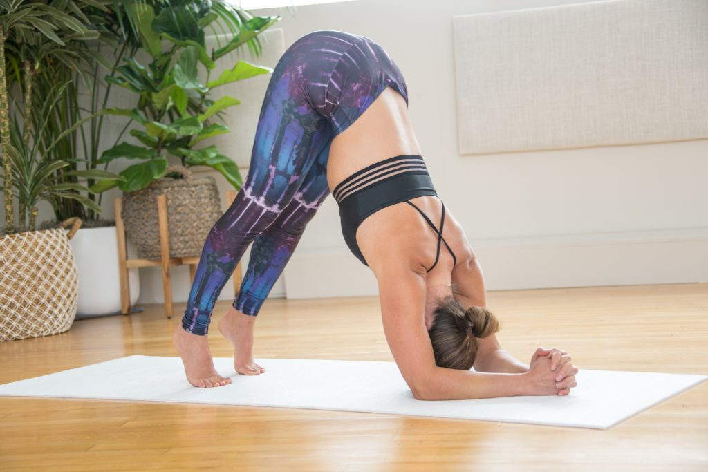 woman practices a modification for headstand inversion
