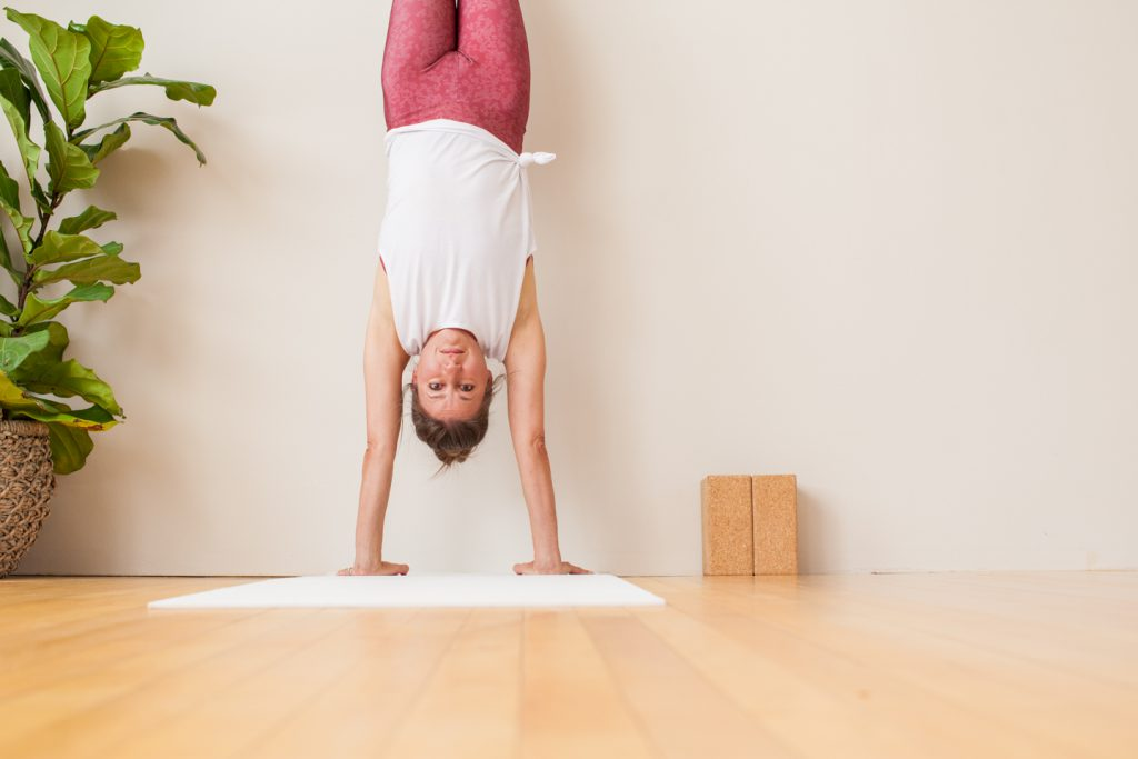 yoga teacher practices a handstand against a wall -yogatoday