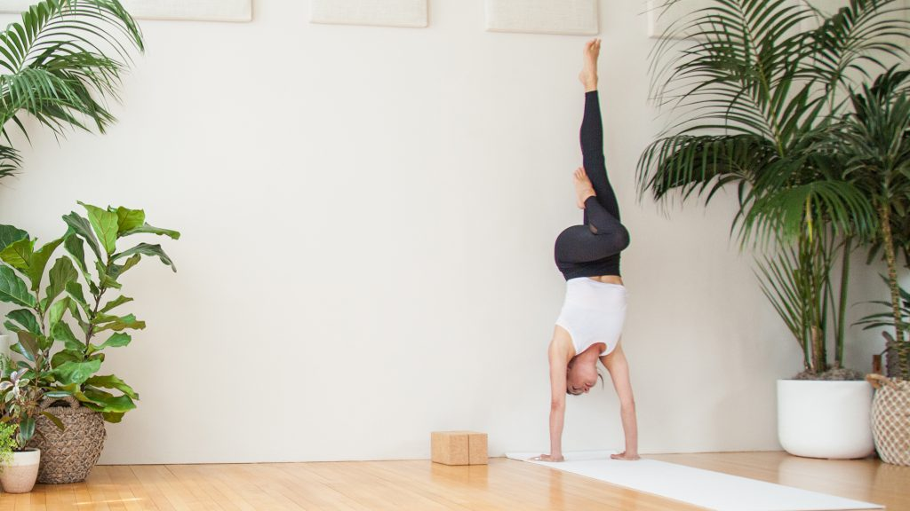 woman practices one legged handstand inversion against a wall -yogatoday