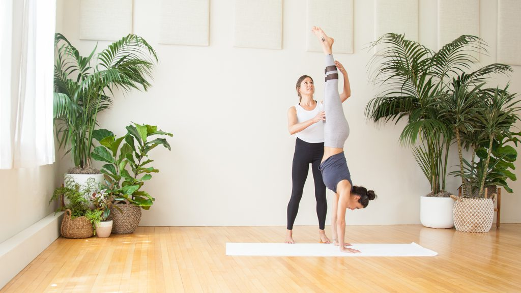 yoga teachers assists a student with an inversion -yogatoday