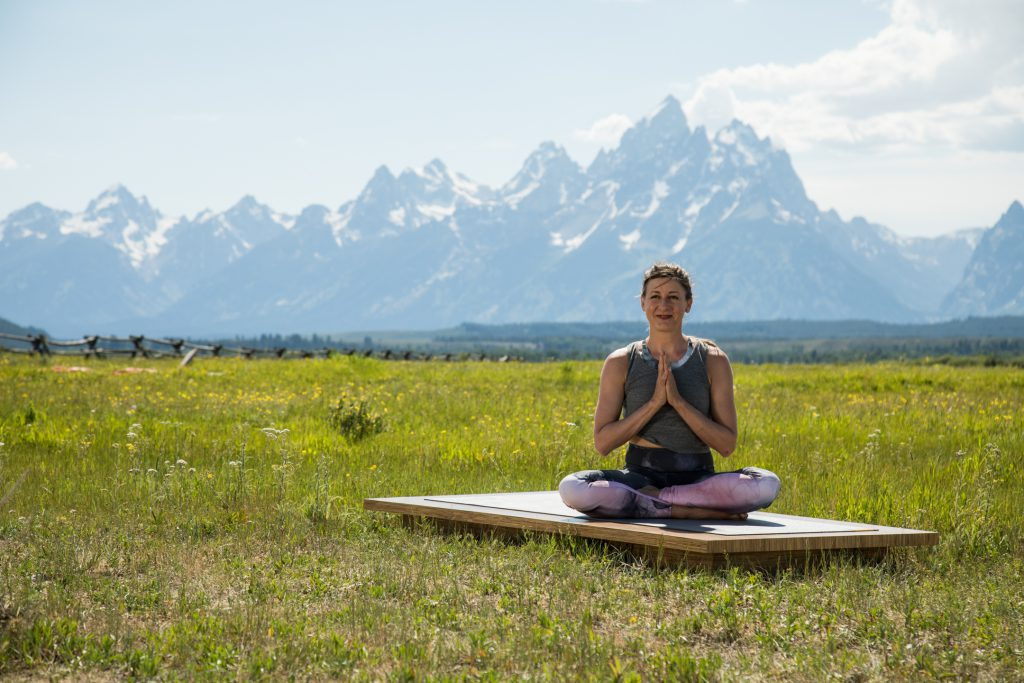 woman seated on a yoga mat outdoors with her hands in prayer position - yogatoday.com