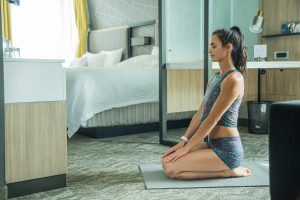 Beautiful woman in a hotel room meditating on a yoga mat.