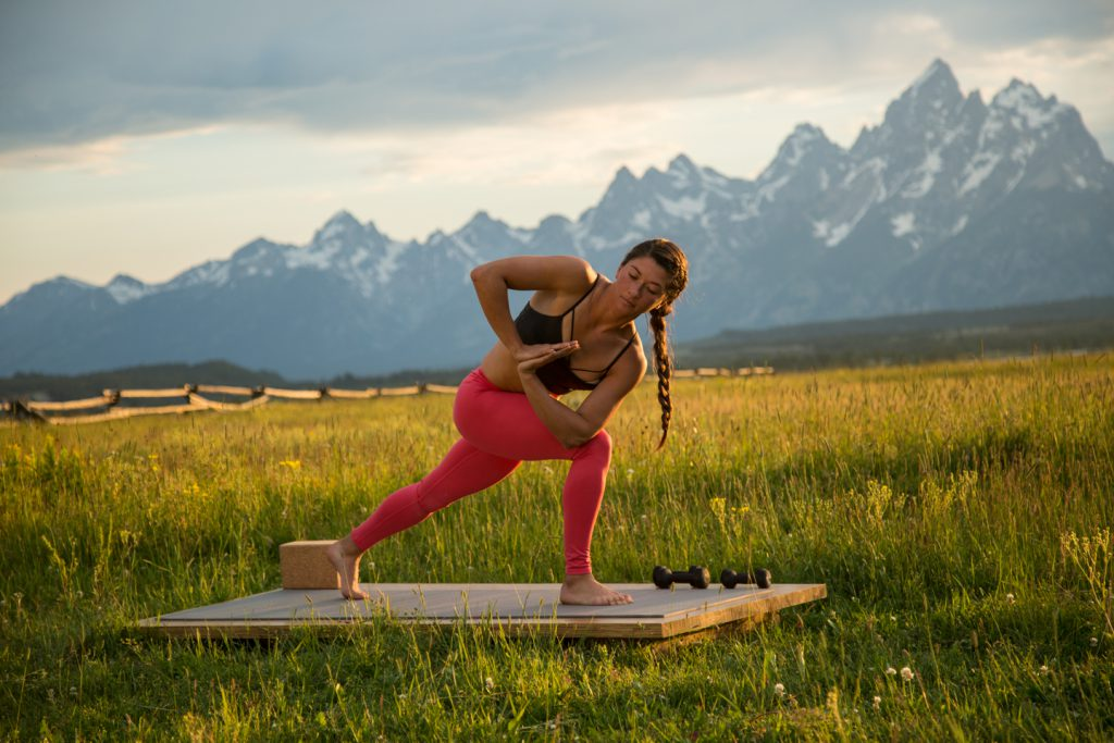 woman practices a twist on an outdoor yoga platform in the Grand Tetons - yogatoday
