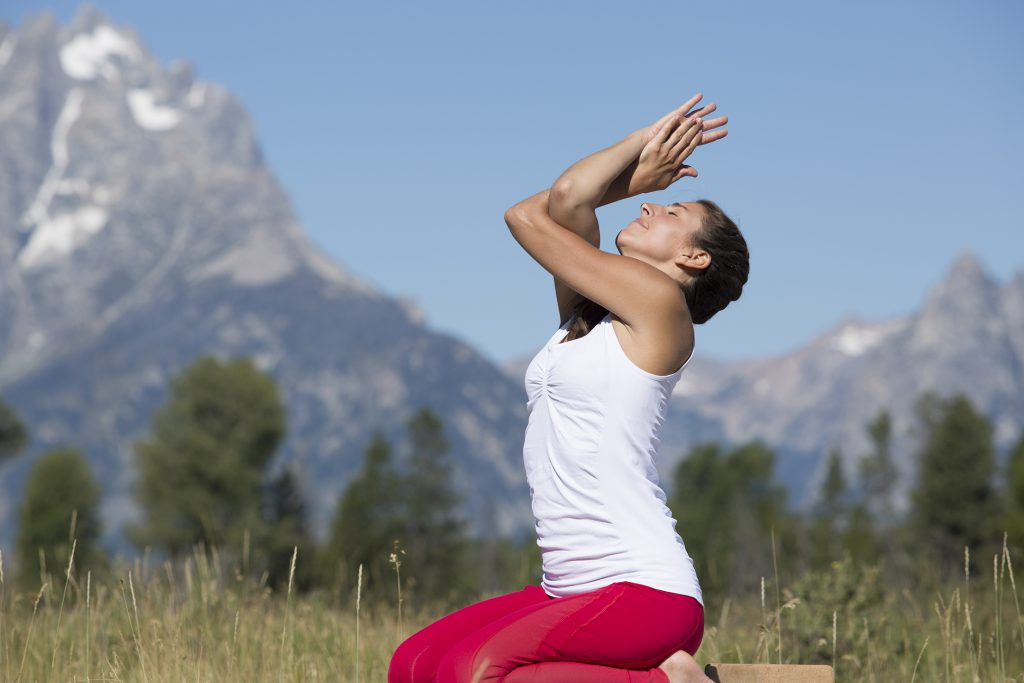 woman practices eagle pose as she does yoga outdoors - yogatoday