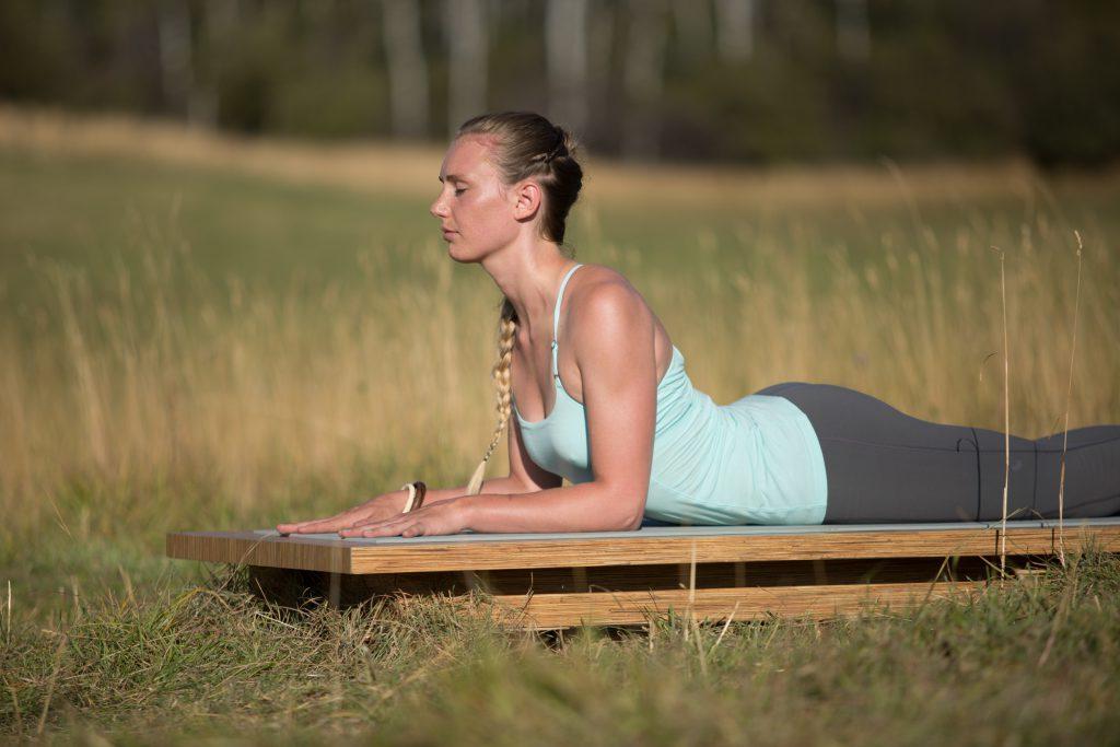 yogi practices sphinx pose outdoors - yogatoday