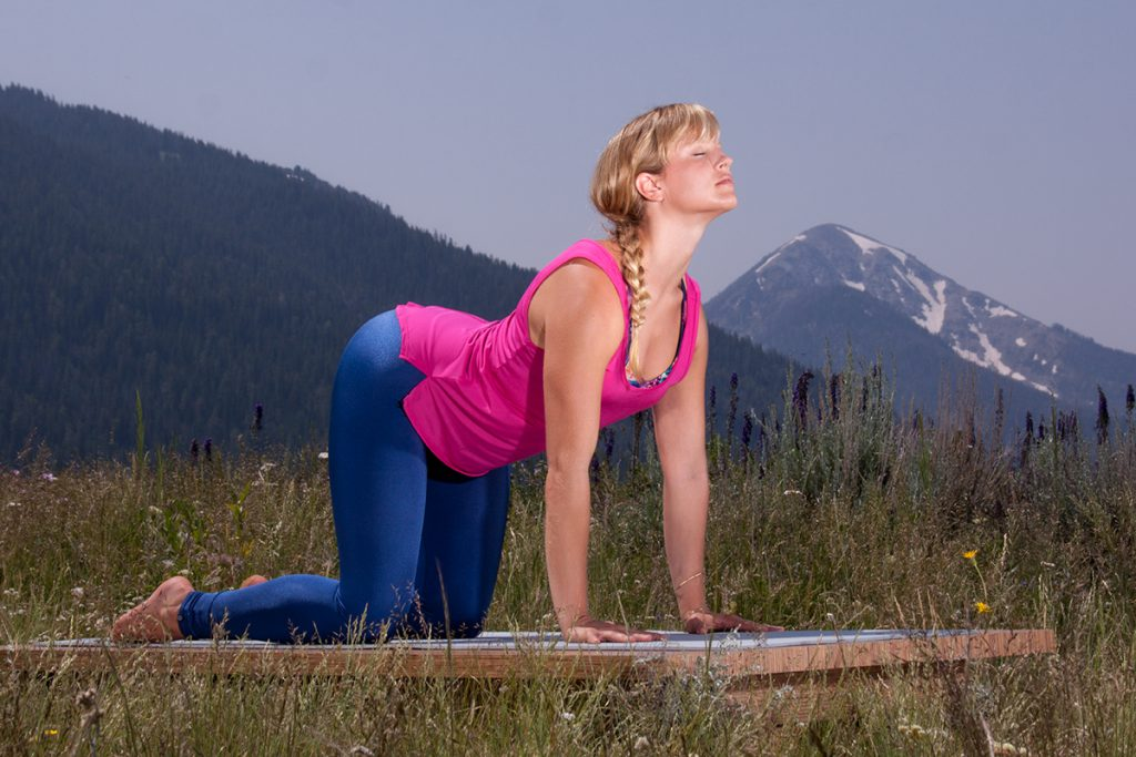 woman practices cat/cow pose to relieve stress - YogaToday