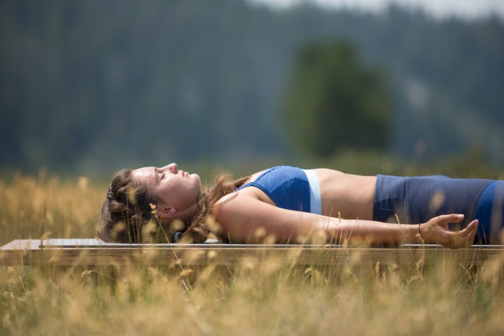 woman practices savasana to relieve stress - YogaToday