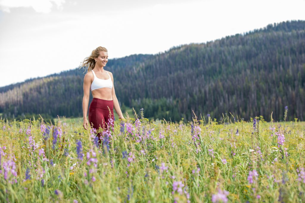 woman walks through a meadow of spring flowers -yogatoday