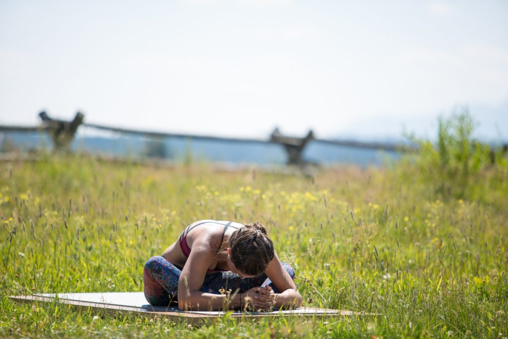 woman stretches outdoors in Grand Teton National Park- YogaToday