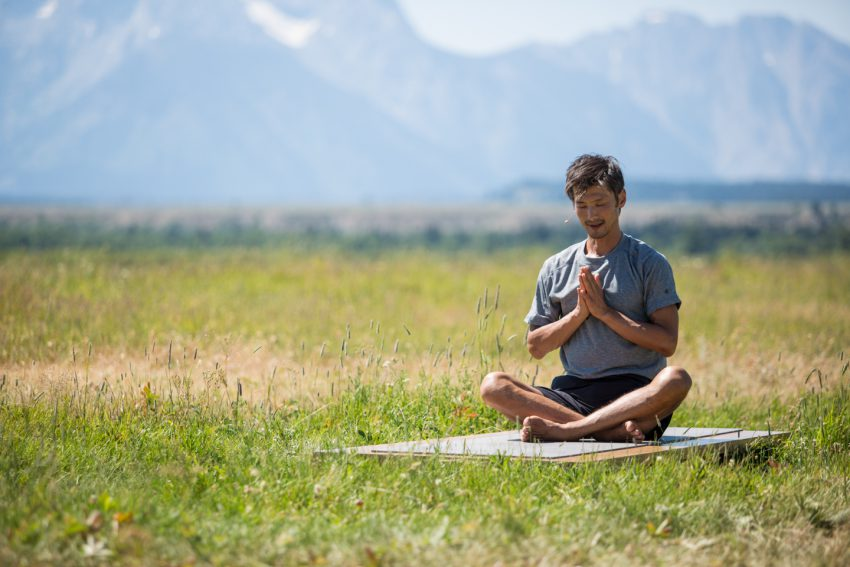 Man Practices Mindfullness Outdoors in Grand Teton National Park -YogaToday