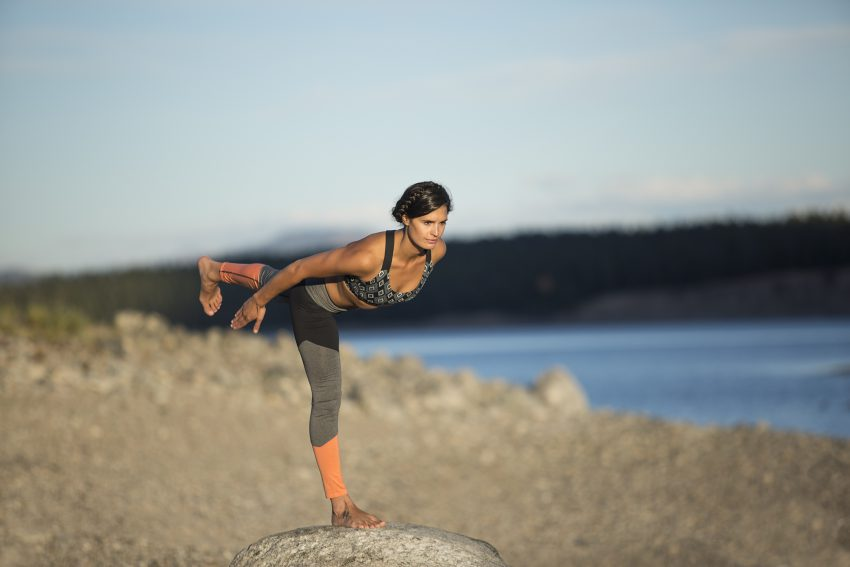 woman practices warrior 3 yoga pose outdoors -YogaToday