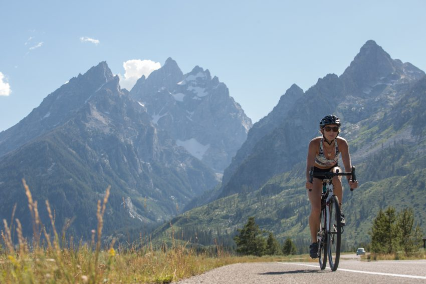 woman cycles in Grand Teton National Park - yogatoday