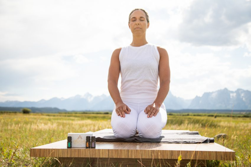 woman practices yoga outdoors with essential oils - yogatoday