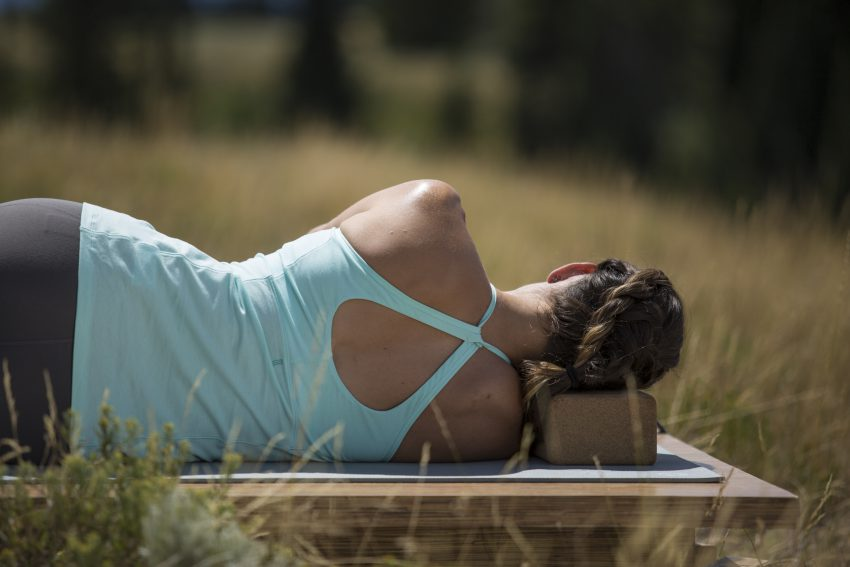 woman practices a yoga pose with the assistance of blocks -YogaToday