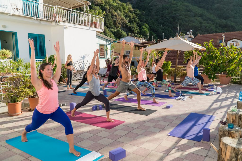 group yoga class flows through standing poses - yogatoday